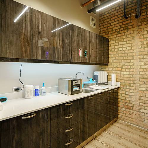 WHOSE WOODS THESE ARE: Dark cabinetry throughout, even in the sterilization area, provides a potent contrast to the walls and flooring.